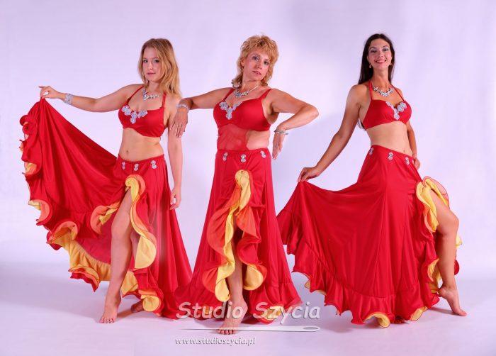 Czerwone suknie zfalbanami dla tancerek orientalnych.Stój taneczny dla siedmiu pań zgrupy tańca brzucha.