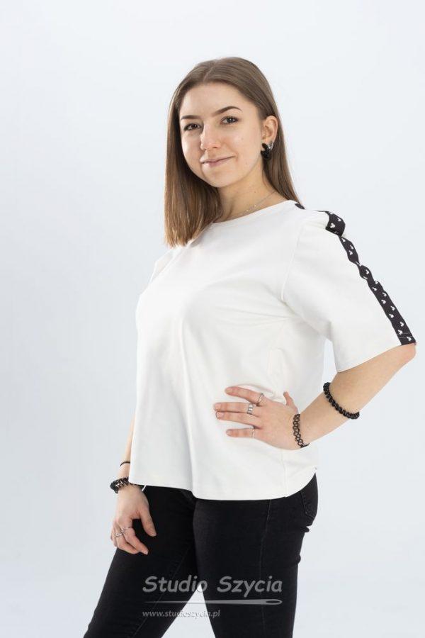 Biała bluzka z czarnym paskiem na rękawie.