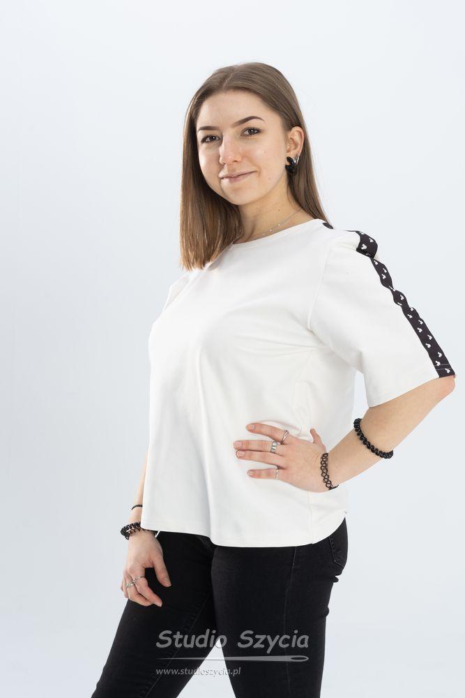 Biała bluzka zczarnym paskiem narękawie.