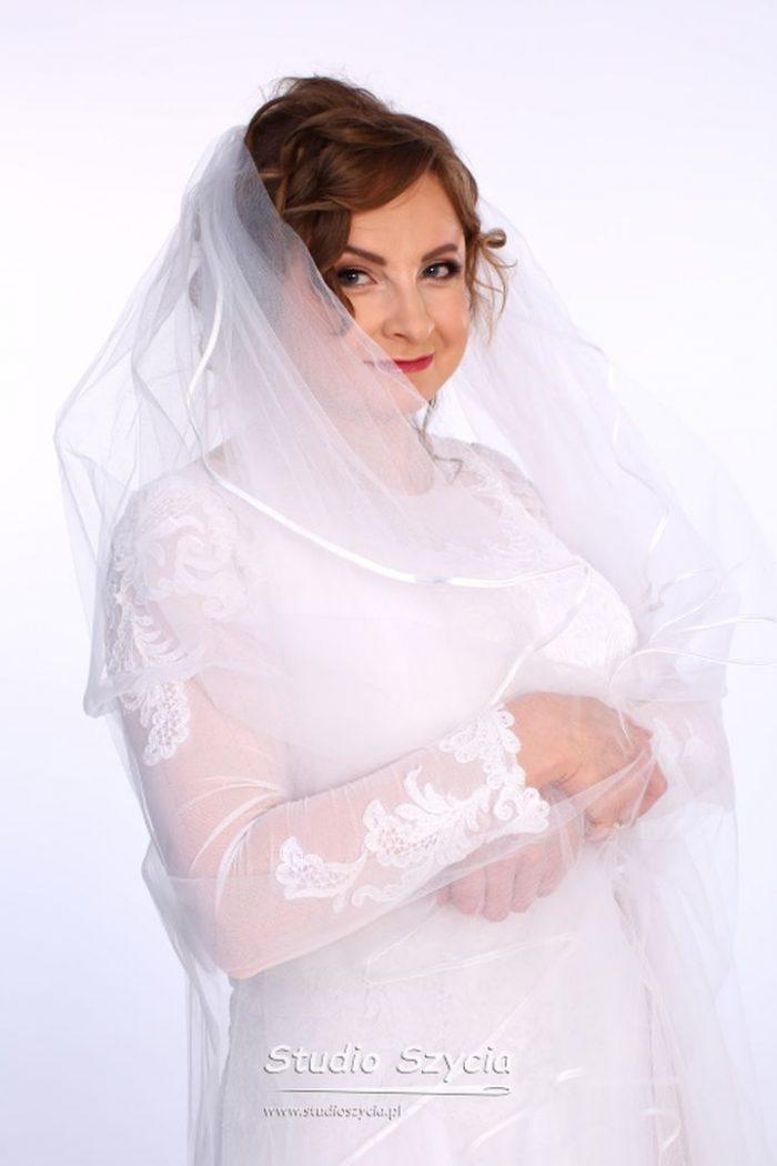 Piękna suknia ślubna wkolorze białym zniewielką kokardą.
