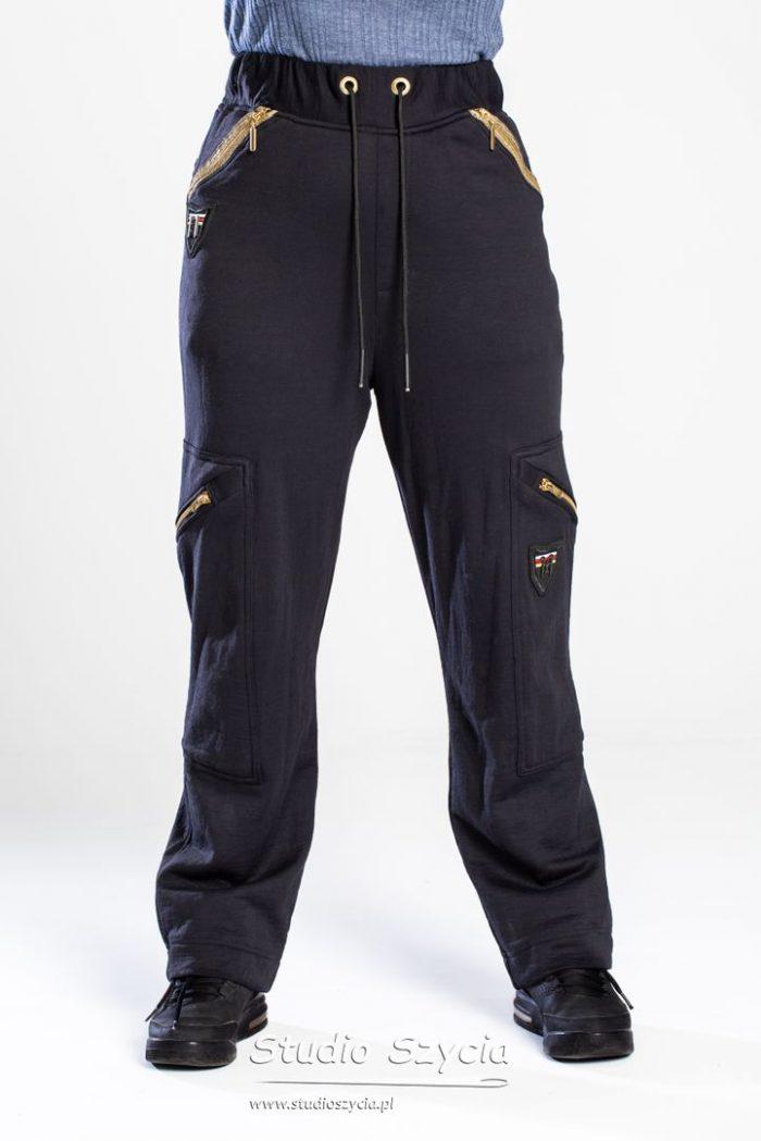 Spodnie dresowe zezłotymi zamkami błyskawicznymi.